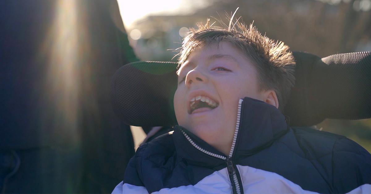 Junge draußen in seinem Rollstuhl in sonnigem Wetter