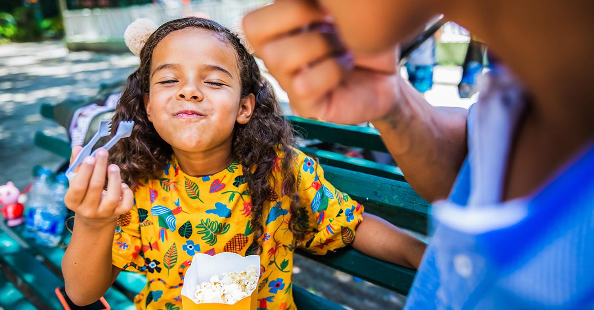 Far och dotter äter popcorn i en nöjespark