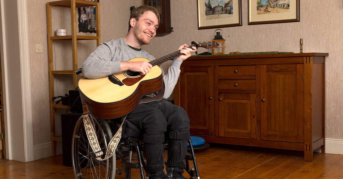 Young man plays his guitar while sitting in his wheelchair
