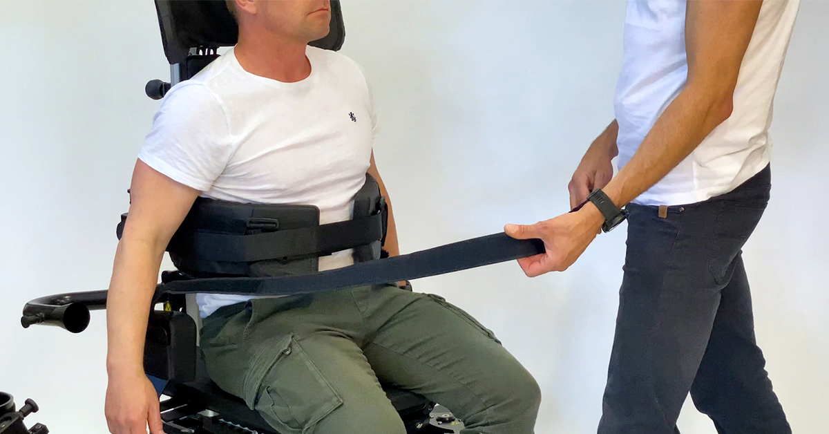 Mann sitter i Innowalk og får strammet hoftebelte