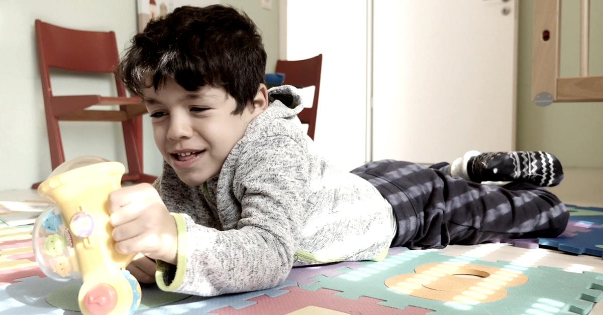 Junge, der auf dem Boden liegt und spielt