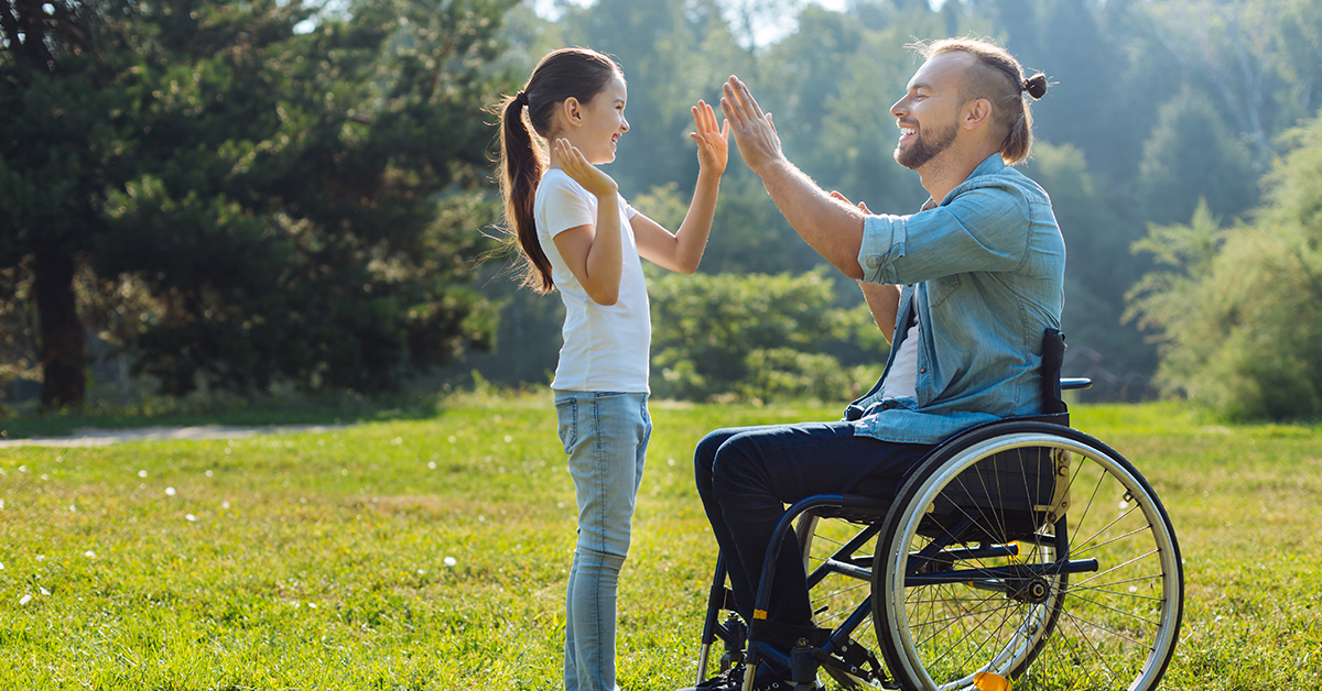 Young father with mobility impairment giving his little daughter a high five.