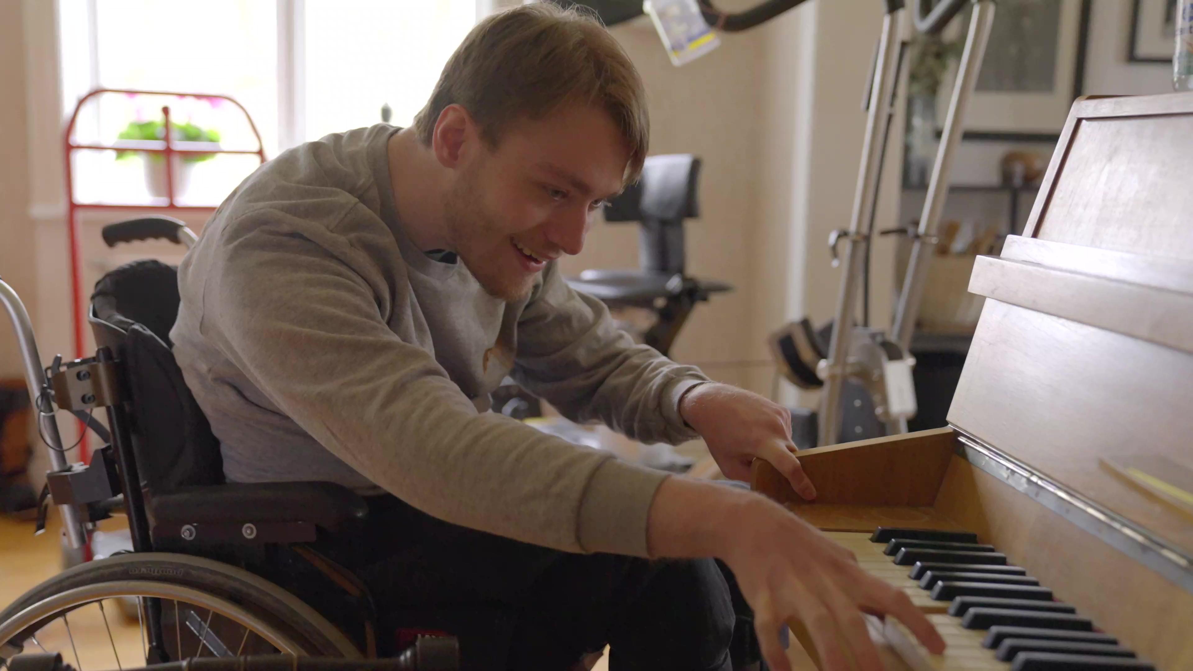 Ung mann spiller gitaren mens han sitter i rullestolen